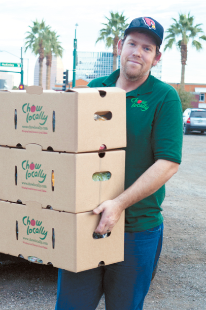 man from Chow Locally carrying produce cartons