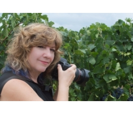 Jenelle Bonifield with camera in the vineyard.